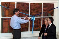 Associate Dean William Baldwin cuts the ribbon with Professor Judith Burton and TC Instructor and muralist Tom Lollar
