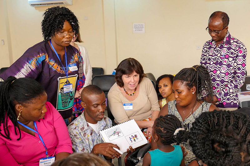 HOUSE CALL Professor Cate Crowley (center, in white) and students from TC's Program in Communication Sciences & Disorders conduct speech therapy for cleft palate patients in Ghana.
