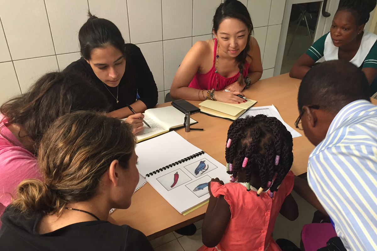 Grad students working with a child on language tasks