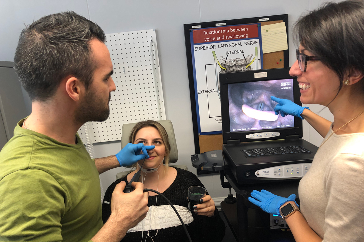 Two researchers measure upper airway disfunction using a scope in their patient