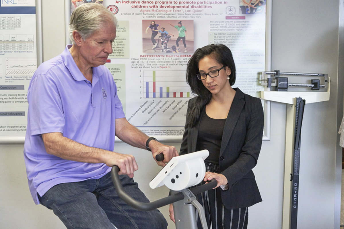 Man on exercise bike with graduate student at research lab