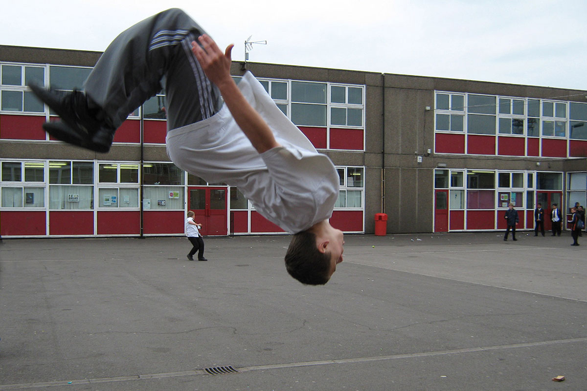 Student flipping on a playground.