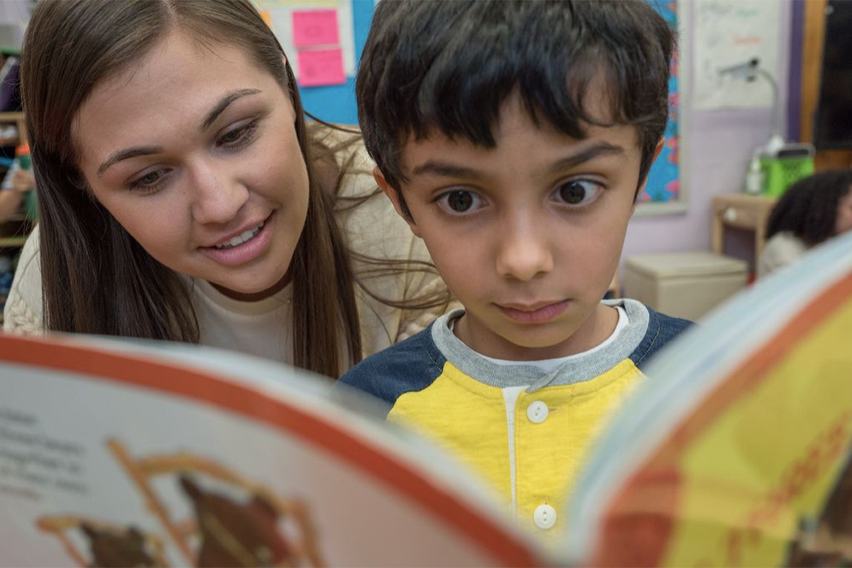 A teacher works with a child on reading a book.