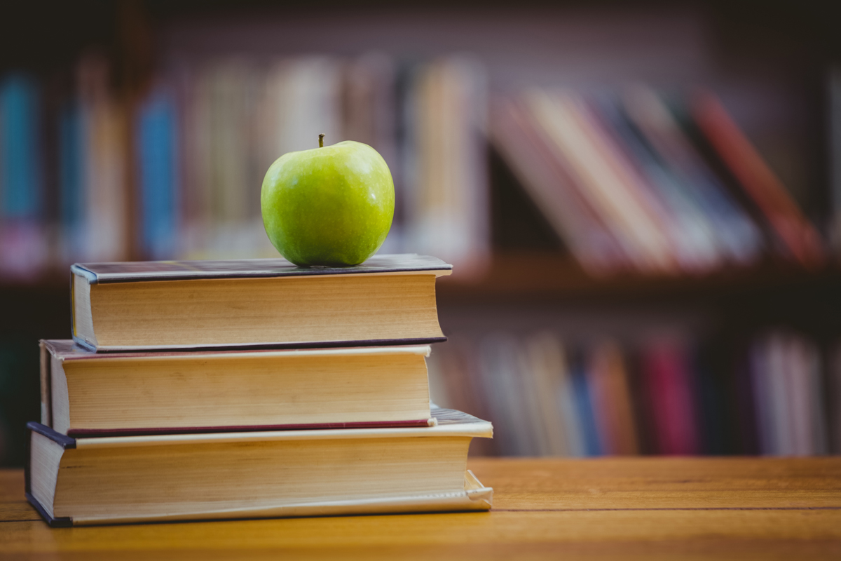 An apple sits on a pile of books with a library shelf in the background