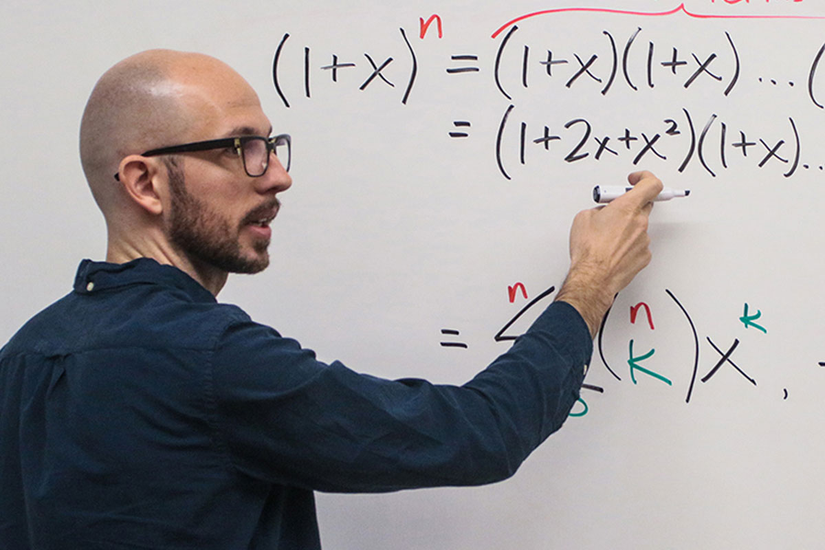Professor Nick Wasserman writes an equation on a white board