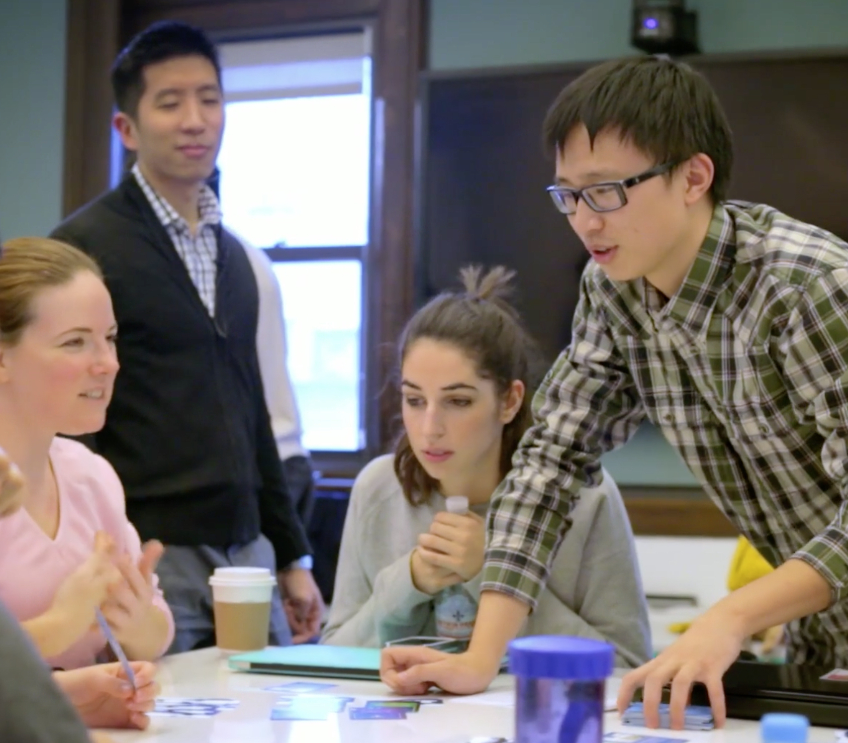 ALPHA PHASE Faculty member Joey Lee (standing, left) with members of a student project team. The teams worked with experienced researchers and mentors to critically examine their process and work.