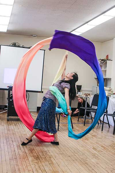 Teaching Artist and TC alumna Ling Tang performs a ribbon dance at a gathering for the Teachers College Teaching Artist Certificate program participants.