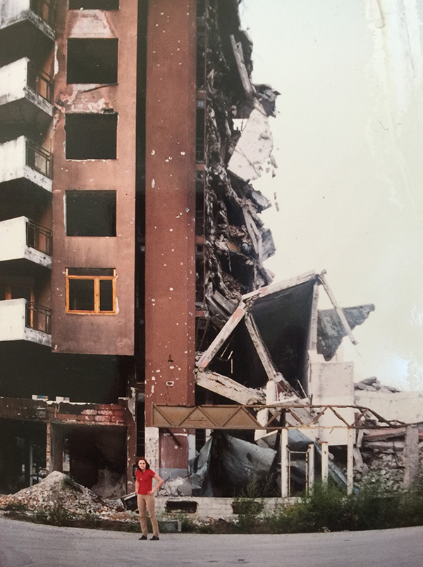 Amra Sabic-El-Rayess standing in front of a bombed-out building in Sarajevo